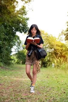 Schöne frau, die kamera um hals hält, reisenotizen schreibt, in einem park geht
