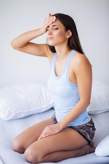 Schöne frau, die krank sich fühlt, kopfschmerzen habend