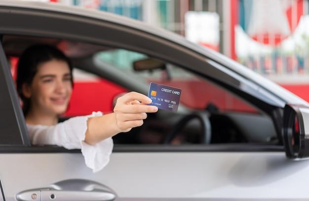 Schöne frau, die kreditkarte hält, um benzin beim tanken an der tankstelle zu bezahlen re