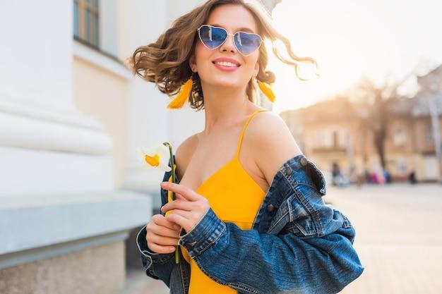 Schöne frau, die lächelndes haar winkt, stilvolle kleidung, jeansjacke und gelbes oberteil tragend, modetrend, sommerstil, glückliche positive stimmung, sonniger tag, sonnenaufgang, straßenmode, blaue sonnenbrille