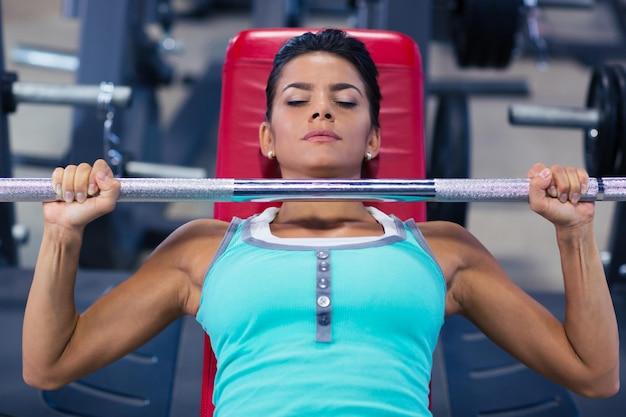 Schöne frau, die langhantel auf der bank im fitness-studio hebt
