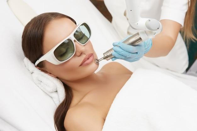 Schöne frau, die laserverfahren auf ihrem kinn erhält, das auf weißem bett in der schutzbrille liegt, attraktive frau im schönheitssalon, die gesichtsbehandlung tut