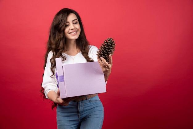 Schöne frau, die lila geschenkbox hält und kiefernzapfen betrachtet foto in hoher qualität