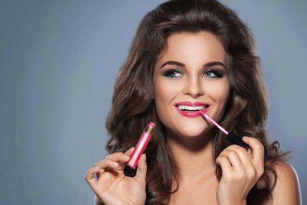 Schöne frau, die lipgloss anwendet