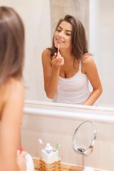 Schöne frau, die lipgloss im badezimmer anwendet