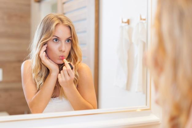 Schöne frau, die lippenstift im badezimmer anwendet