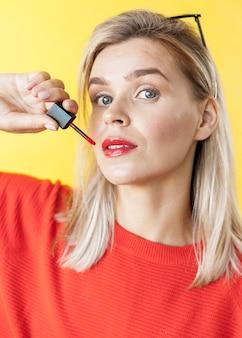 Schöne frau, die lippenstiftabschluß oben anwendet