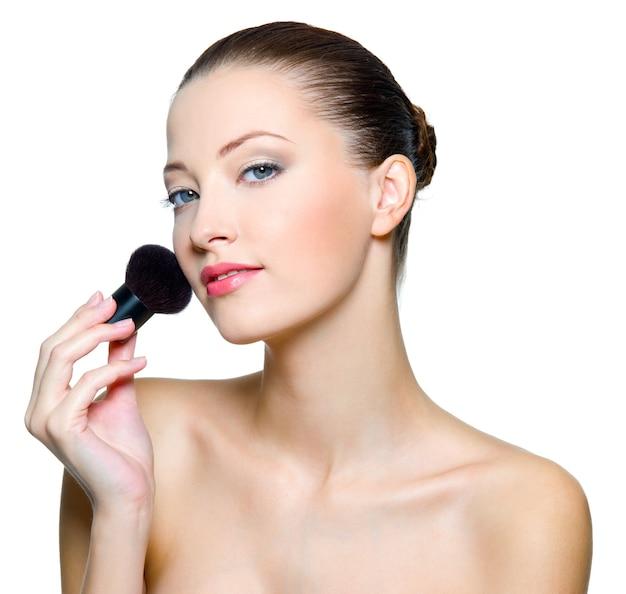 Schöne frau, die make-up auf gesicht mit kosmetischem pinsel tut.