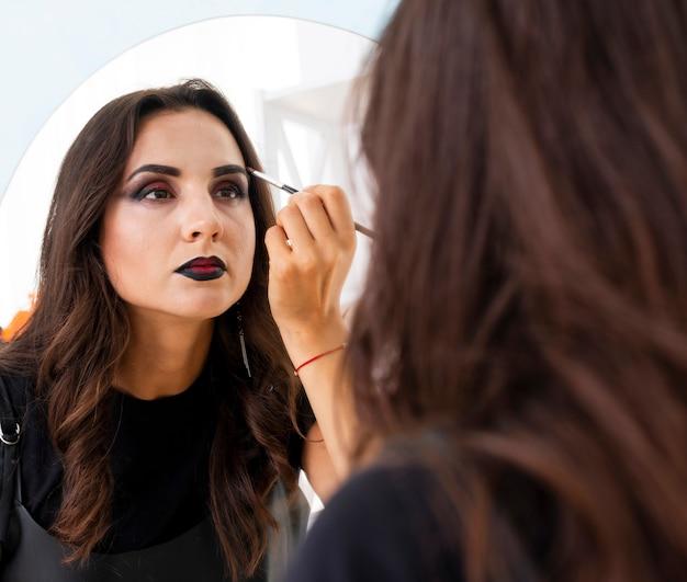 Schöne frau, die make-up für halloween vorbereitet
