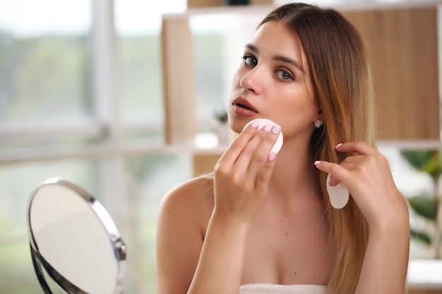 Schöne frau, die make-up im schönheitskonzept anwendet