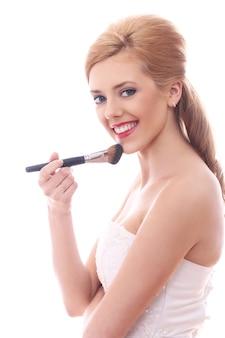 Schöne frau, die make-up mit pinsel aufträgt