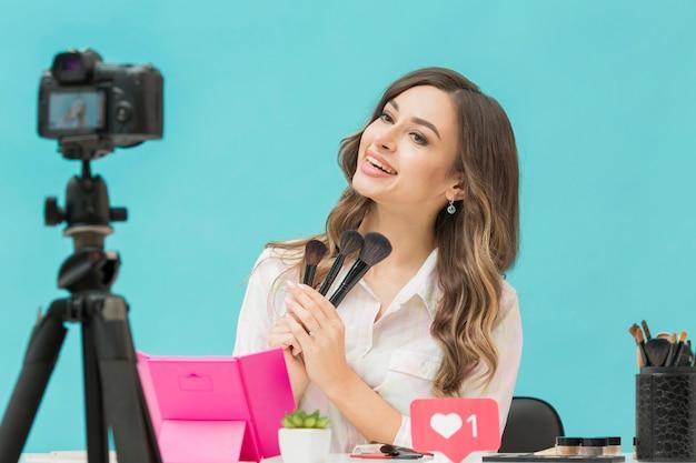 Schöne frau, die make-up-video aufzeichnet