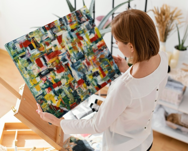 Schöne frau, die mit acryl auf leinwand malt