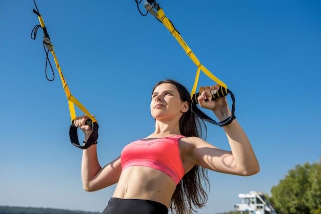 Schöne frau, die mit aufhängebändern trx im freien nahe dem see zur tageszeit trainiert. gesunder lebensstil