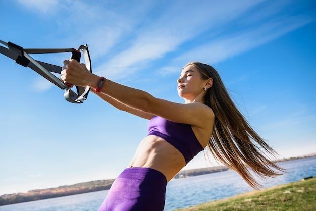 Schöne frau, die mit aufhängungsgurten trx im freien nahe dem see zur tageszeit trainiert. gesunder lebensstil