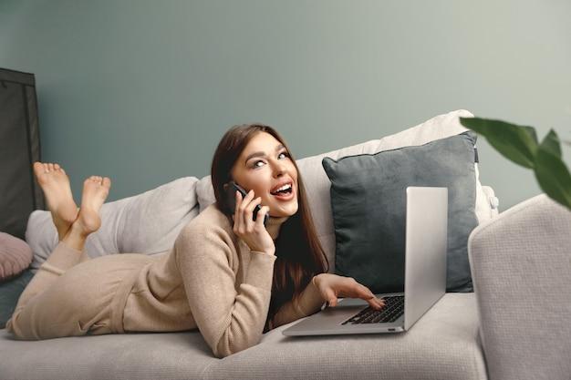 Schöne frau, die mit dem handy spricht, während sie einen laptop für die fernarbeit verwendet junge frau, die mit einem laptop auf der couch arbeitet online-shopping zahlung