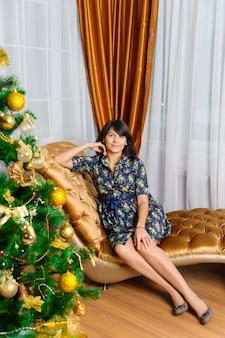 Schöne frau, die mit dem weihnachtsbaum aufwirft