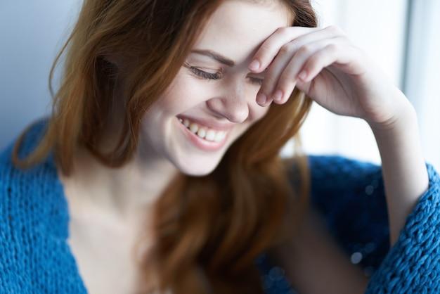 Schöne frau, die mit einem blauen karierten lächeln auf der fensterbank sitzt