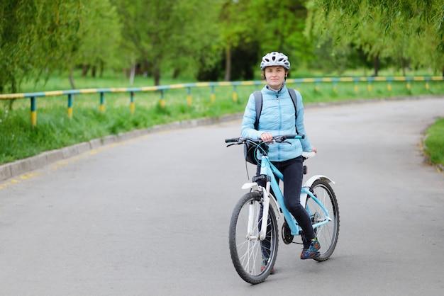 Schöne frau, die mit einem fahrrad auf der straße steht