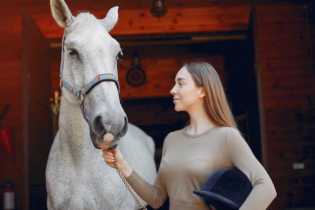 Schöne frau, die mit einem pferd steht