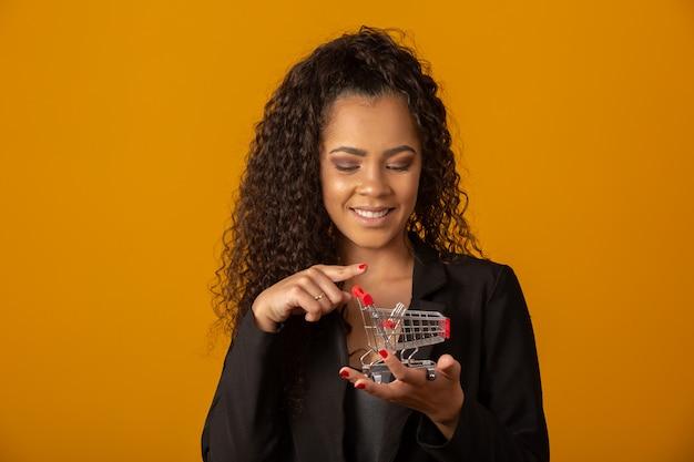 Schöne frau, die mit einer afrofrisur lächelt und einen kleinen einkaufswagen anhält
