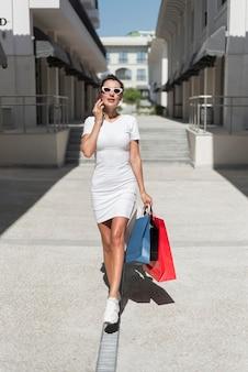Schöne frau, die mit einkaufstaschen aufwirft