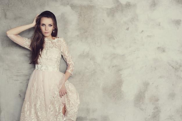 Schöne frau, die mit elegantem weißem kleid, wandkopyspace aufwirft