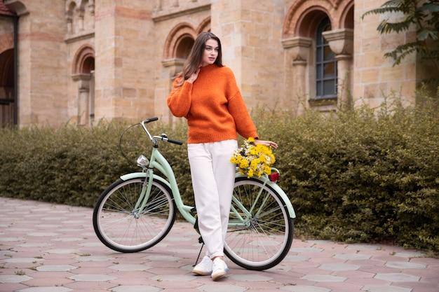 Schöne frau, die mit fahrrad und blumen draußen aufwirft