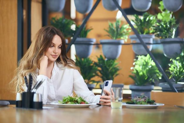 Schöne frau, die mit freunden auf modernem telefon chattet