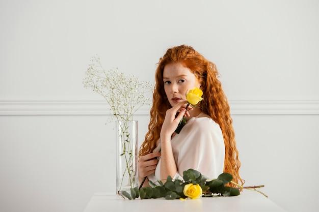 Schöne frau, die mit frühlingsblumen und vase aufwirft