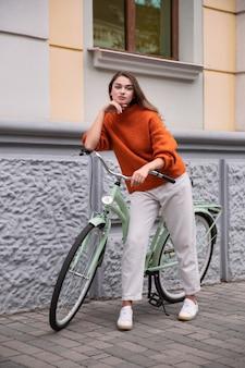 Schöne frau, die mit ihrem fahrrad in der stadt aufwirft