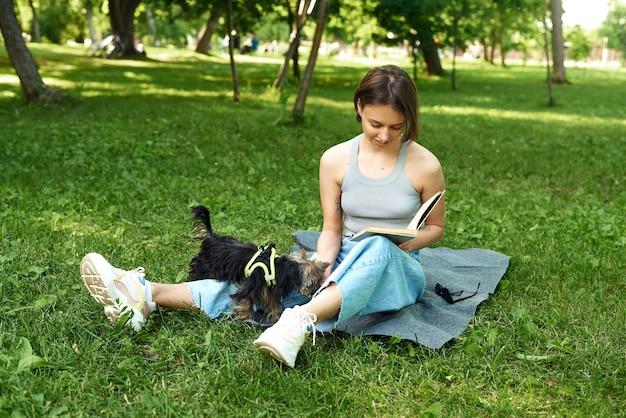 Schöne frau, die mit ihrem hund draußen genießt.