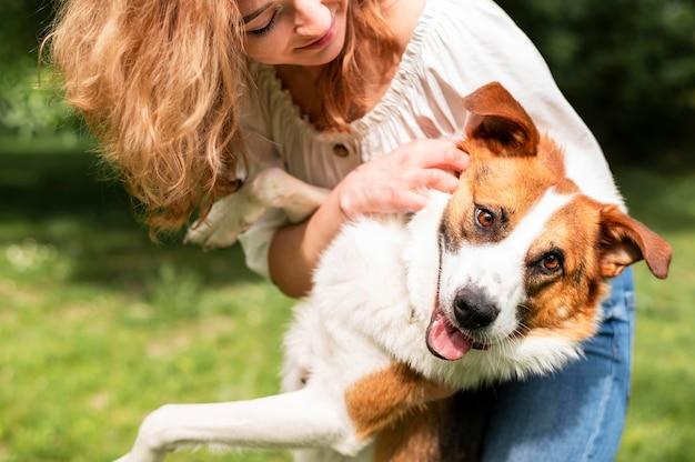 Schöne frau, die mit ihrem hund im park spielt