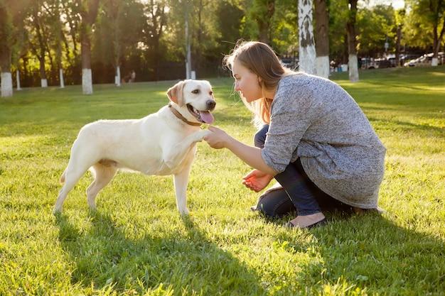 Schöne frau, die mit ihrem hund spielt