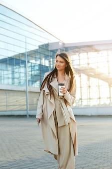 Schöne frau, die mit kaffee geht, der nahe bürogebäude geht. porträt der erfolgreichen geschäftsfrau