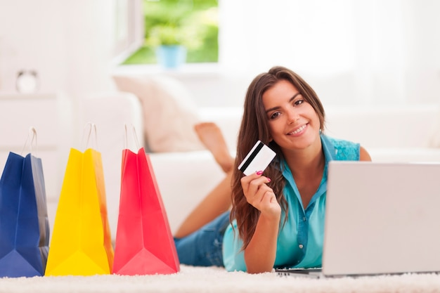 Schöne frau, die mit kreditkarte für das einkaufen zu hause zahlt