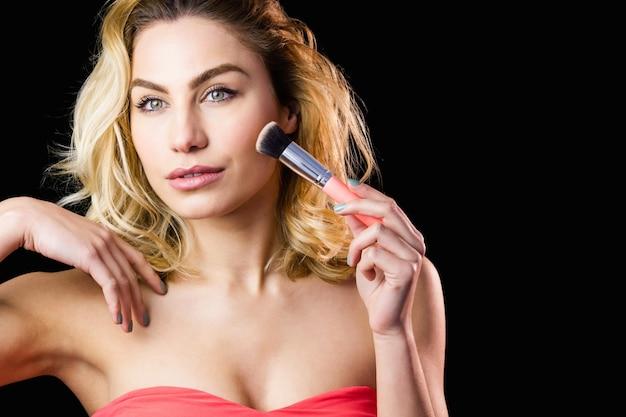 Schöne frau, die mit make-up pinsel aufwirft