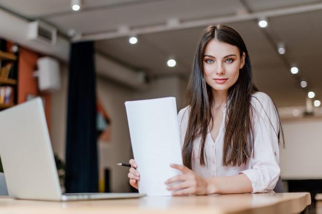 Schöne frau, die mit papieren und laptop im büro arbeitet