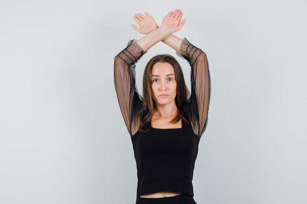 Schöne frau, die mit verschränkten armen über kopf in der vorderansicht der schwarzen bluse aufwirft.