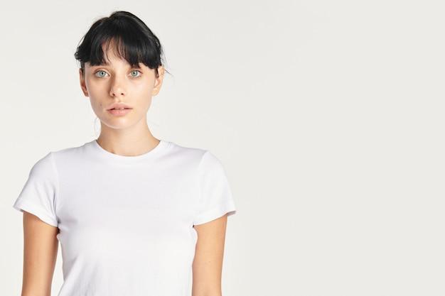 Schöne frau, die mit weißem leerem hemd, kopienraum aufwirft