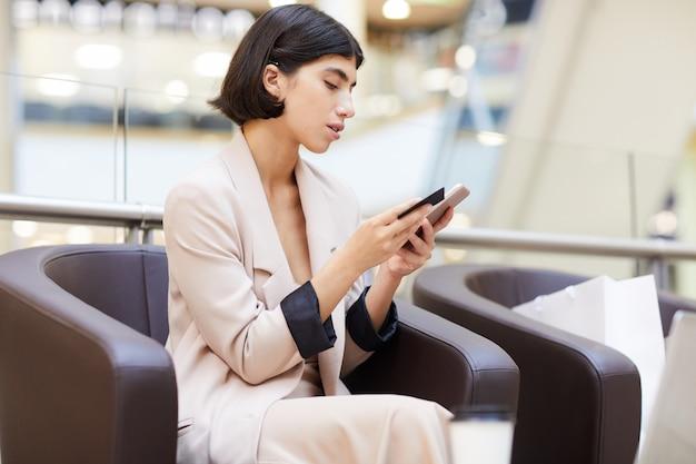 Schöne frau, die mobile app in mall verwendet