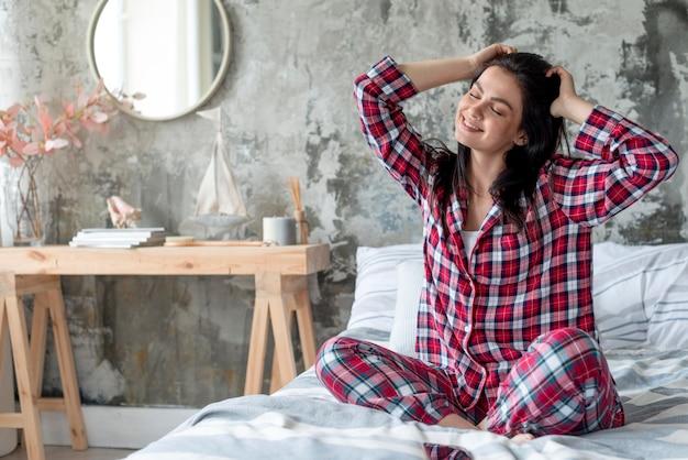 Schöne frau, die morgen im pyjama genießt