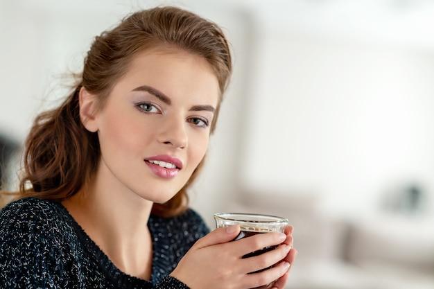 Schöne frau, die morgens zu hause kaffee trinkt