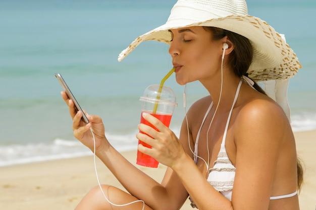 Schöne frau, die musik am strand hört