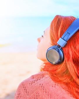 Schöne frau, die musik auf dem strand hört. junge frau, die musik mit kopfhörern hört.