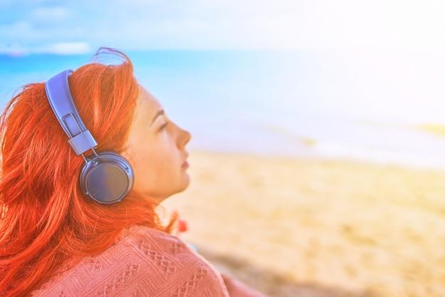 Schöne frau, die musik auf dem strand hört.