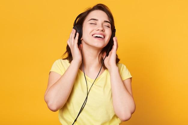 Schöne frau, die musik auf gelber wand hört. charmante dame posiert mit geschlossenen augen, hört gerne lieblingsmusik, hält kopfhörer in der hand, singt und entspannt sich. lifestyle-konzept.