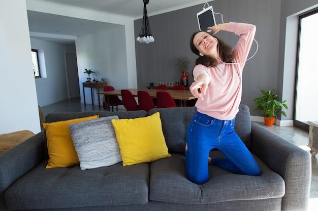 Schöne frau, die musik hört und auf sofa tanzt