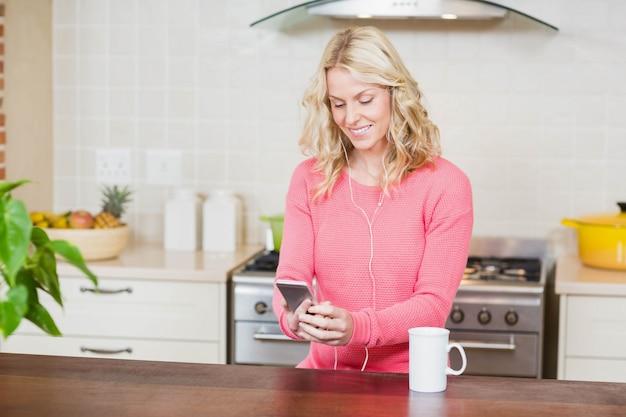 Schöne frau, die musik in der küche hört