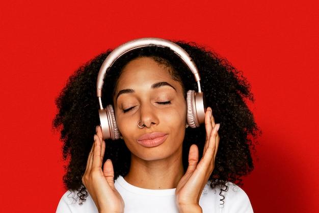 Schöne frau, die musik über digitales kopfhörergerät hört